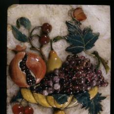 Placa con taza que contiene frutas y mariposa