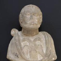 Busto masculino con un águila bicéfala en el pecho y escudo eclesiástico en la peana