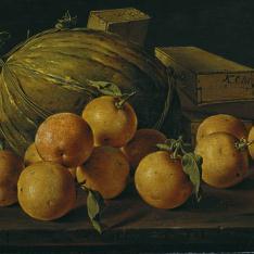Frutero con naranjas, melón y cajas de dulce