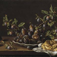 Frutero con ciruelas en un plato, higos y una rosca