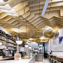 Undulating plywood ceiling perfects movement and acoustics in Madrid restaurant