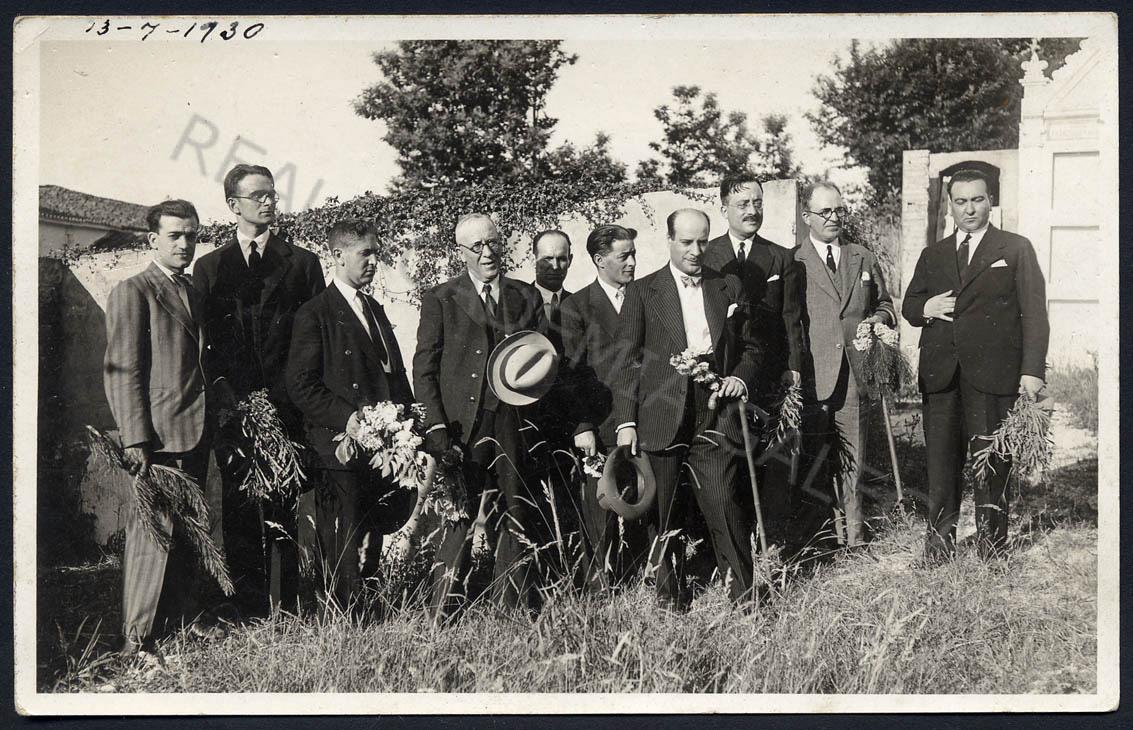 Foto en blanco y negro de un grupo de hombres con flores en la mano